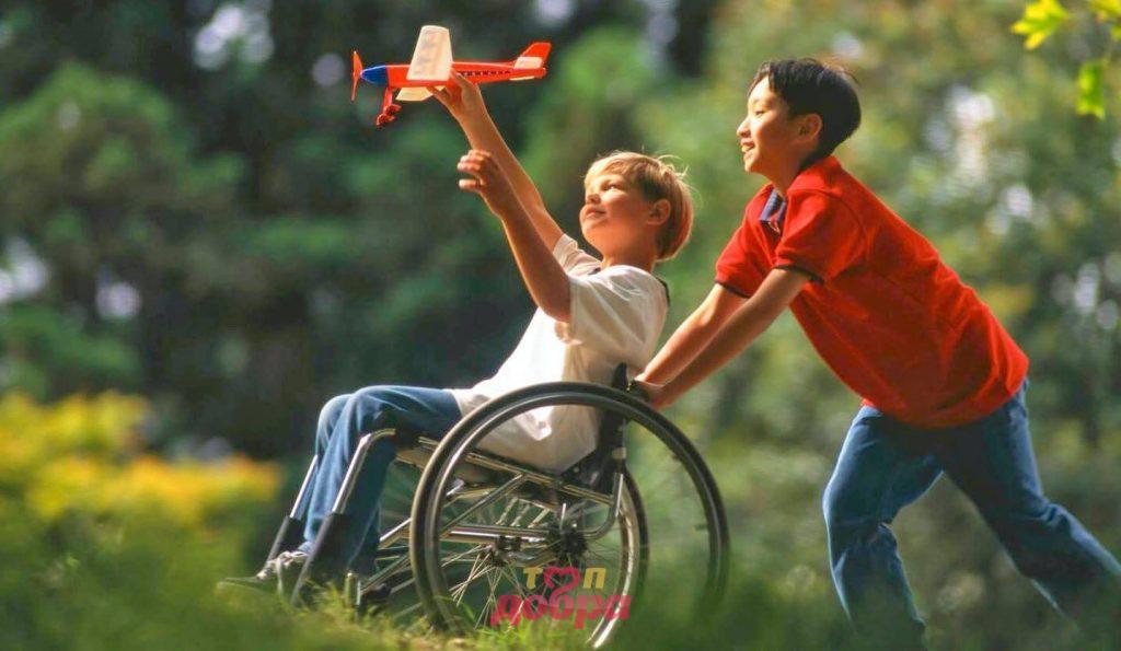 мальчик катает своего друга на инвалидной коляске